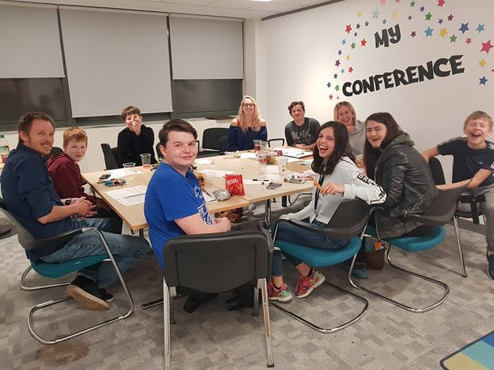 A group of 9 young people and one member of the SYAS staff are sat inside a room, around a conference table. They are all looking at the camera happily. There are drinks, snacks and pieces of paper on the table. On one wall there are star sticks and words that read: my conference.