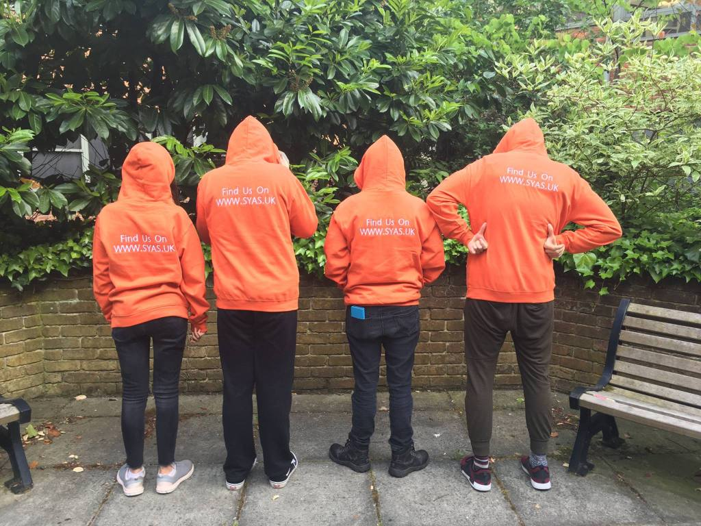 Four people stand side-by-side outside on a patio, with their backs facing the camera. They are wearing bright Orange hoodies with the hoods up. On the back of the hoodies it reads: Find us on www.SYAS.uk and they are also all wearing dark trousers.