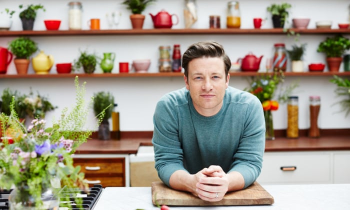"""Jamie Oliver is picture leaning on a chopping board on a kitchen counter top. Wearing a blue-green sweat-shirt with his short hair brushed back, Jamie Oliver stares straight at the camera. The kitchen is tidy but decorated in a maximalist style using bowls, jugs, kettles, storage containers and plants."""