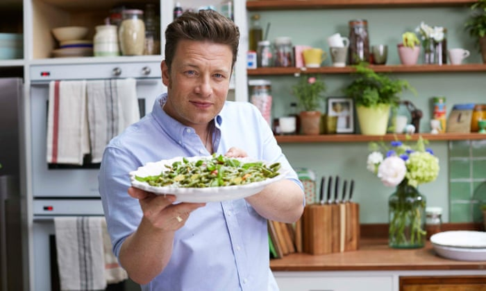 Jamie Oliver stands giving eye contact to the camera and offering a plate of food forward. Wearing a blue shirt, with his short hair brushed back, Jamie Oliver is seen in what looks like a home kitchen.