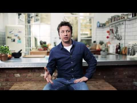 Jamie Oliver can be seen sitting on a stool in mid-conversation. He is wearning blue jeans and a dark blue shirt. His hair is ruffled. The background is a blurred out, large kitchen with big windows.