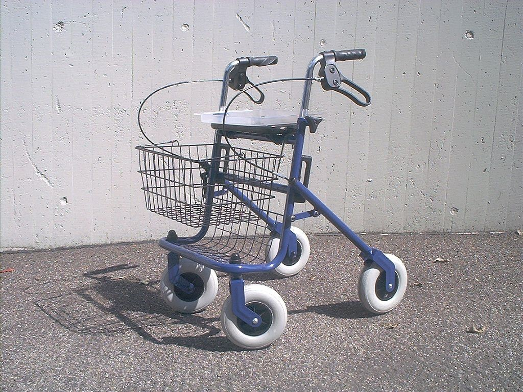 A picture of a blue framed rollator with a black basket. It has four white wheels and a seat above and behind the basket.