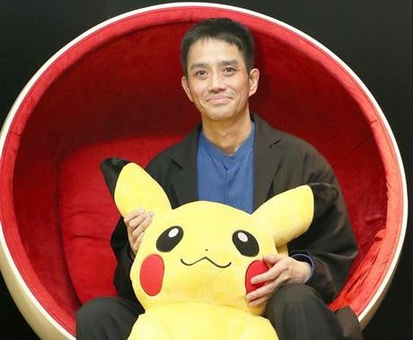 Image Description: The creator of Pokémon, Satoshi Tajiri picture with a plush Pikachu. He is sitting in an egg chair that is red on the inside. He is wearing a black blazer with a blue top and black trousers. He is holding a large pikachu plush toy between his legs.
