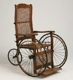 A drawing of an 19th century wooden wheelchair. The two front wheels are large, with one small back wheel. There is also a foot rest