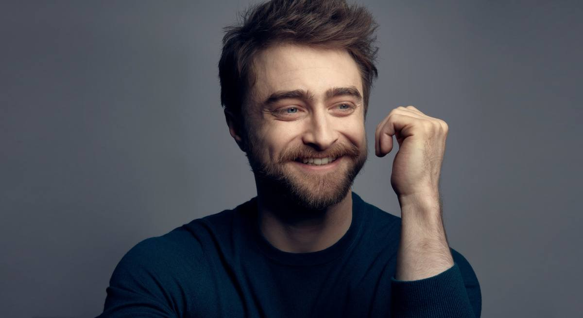 A close up photograph of Daniel Radcliffe's face. He is smiling and looking off to the right hand side. He has a neat short beard and his short brown hair is styled to stand on end. He is wearing a blue crew-neck, long sleeve top. His left arm is held up by his face, but not touching it, his hand curled into an open fist.