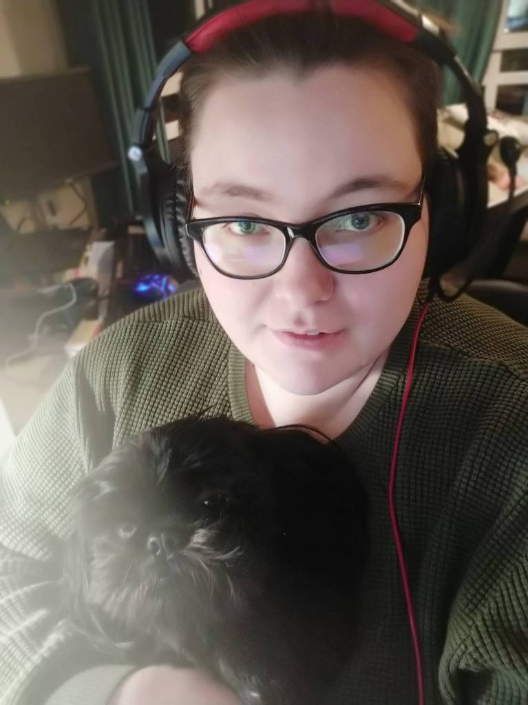 A selfie of Sabrina and her dog, Relic. She is wearing thick rim glasses, a dark green jumper and her hair is tied back. She is wearing an over ear headphone and mic set that is red and black. Relic the dog is black and long haired.
