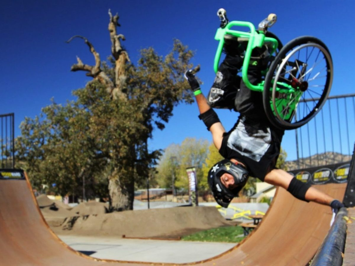 Aaron Fotheringham on a green wheelchair, wearing a helmet. He is upside down in the air with his hand on the edge of a half pipe.