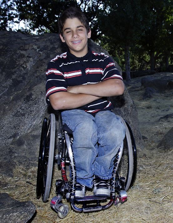 A young Aaron Fotheringham sitting in his wheelchair smiling with his arms crossed. He is wearing a navy blue, red and white stripped polo shirt with blue denim jeans. In the background behind him is a large rock and some trees.