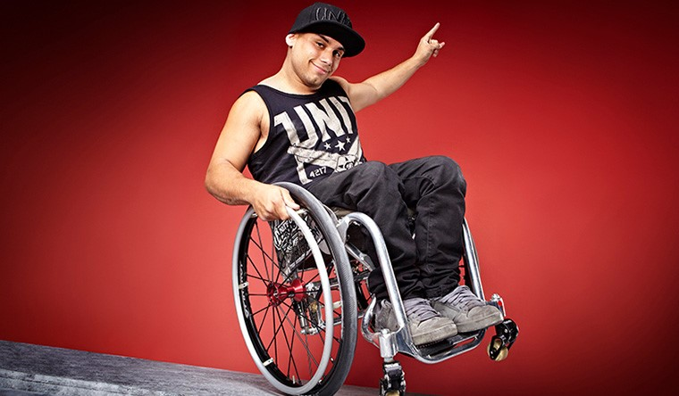 Aaron Fotheringham in his wheelchair on one back wheel doing a wheelie, smiling and his arm to the side and his hand with his pointing finger pointing up. He is wearing black denim jeans, a black vest top with decorative imaging on it, dirty white trainers and a black cap on his head. The background is red.