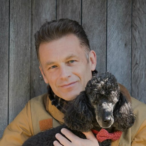 A smiling Chris, holding one of his Poodle dogs in his arms.
