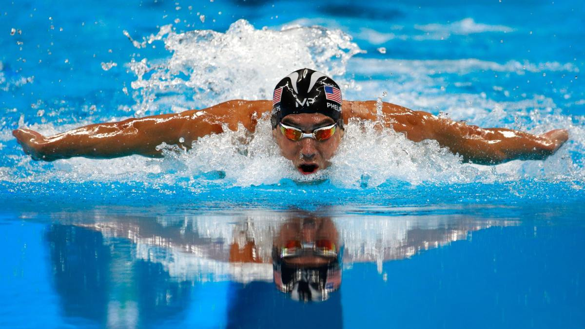 Michael Phelps swimming through the water in a pool towards the camera. He is wearing a swimming cap and goggles.
