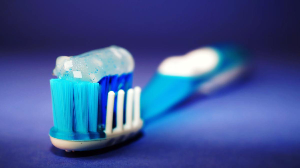 A blue toothbrush on a blue background with toothpaste on the bristles.