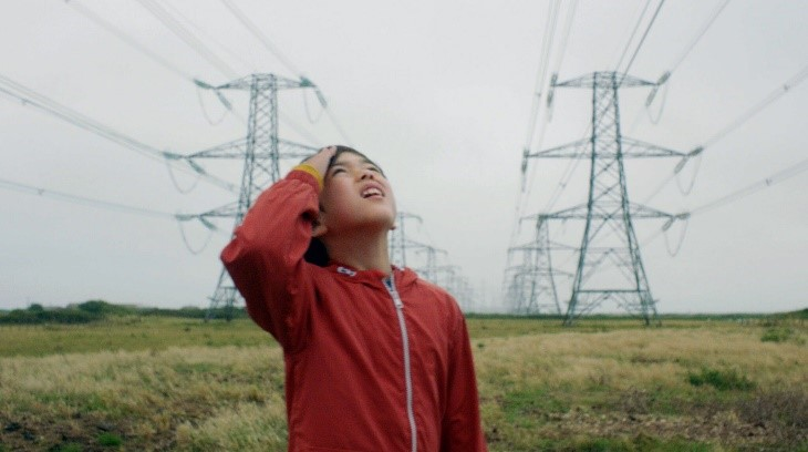 Screenshot from the film the reason I jump. Young boy is looking up towards the sky. He is wearing a red raincoat. In the background there are pylons.