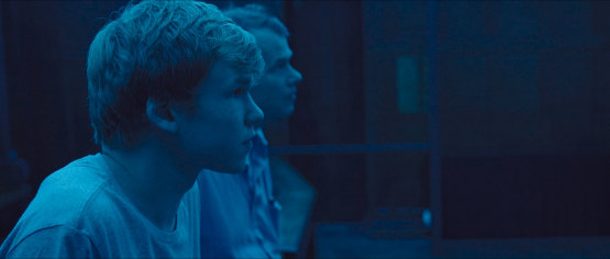 A screenshot from the film the reason I jump. Everything is in tones of blue. You can see a young man in the forefront looking to the right. A behind him another man looking the same way.